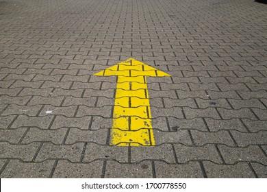 Simple straightforward solution concept: Yellow arrow an paving blocks showing direction straight ahead