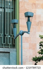 A simple street lamp on the background of a building.