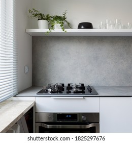 Simple style kitchen with gray countertop, white cupboards and kitchen hob with oven