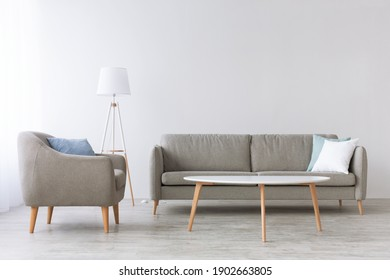 Simple style, scandinavian design and empty living room at home. Sofa with blue and white pillows and armchair on wooden floor, lamp and white table, on light wall background in daylight, nobody