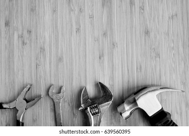 Simple Tool Background. Pliers, spanner, adjustable wrench and hammer on workbench in black and white