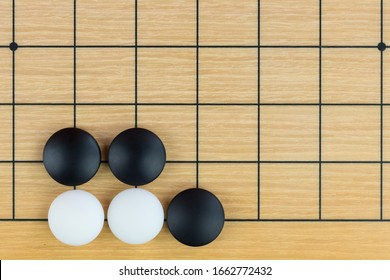 Simple training position of black and white stones on the playing field (gohan) of Chinese game go - traditional Chinese strategy board game.
