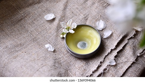 Simple Vegan Healing balm. Homemade healing salve on the fabric background surronded with cherry flower petals. Clean leaving.