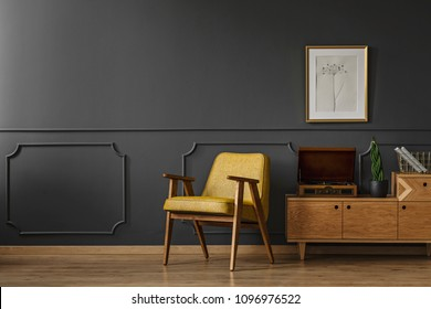 Simple vintage living room interior with black walls, wooden floor, yellow chair, gramophone and poster