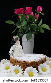 Simple wedding anniversary cake surrounded by artificial flowers decorated with an old figurine bridal pair in front of a vase with red roses isolated in front of black background