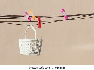 Simple white basket with clothespins, doing the loundry