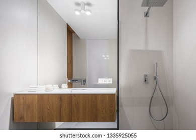 Simple, white bathroom with shower and wooden basin cabinet