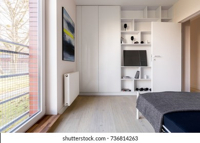 Simple white bedroom with bedroom, bookcase and wardrobe