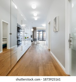 Simple and white corridor in loft apartment with wooden floor, mirrored wardrobe and stylish ceiling light