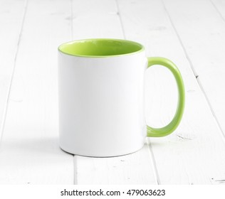 simple white cup with green inside and handle on white wooden background