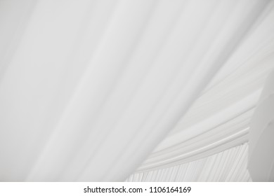 Simple white fabric tulle covers ceiling of event space.