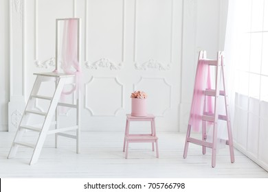 Simple white interior, pink ladder decor and flowers in the box.
