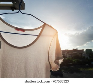Simple white T-shirt hanging dry at apartment balcony after laundry with bright sunlight shining from behind.