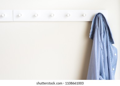 Simple white wall coat hanger with a hanging shirt