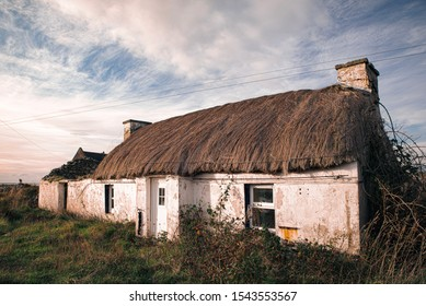 Simple white washed Irish cottage, abandoned and left to the elements.