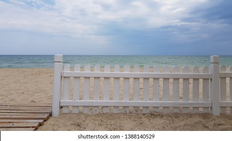 Simple white wood fence on beach sand with sea and clouds background. Minimal summer seascape with wooden beach path. Summer sea vacation. Coastal landscape with white striped fence and striped path