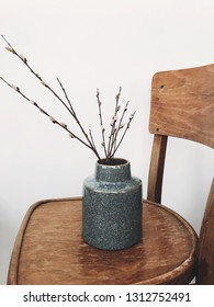 Simple willow buds branches in stylish vase on wooden rustic chair in home. Hello spring concept. Countryside living. Modern rural still life. Easter decorations