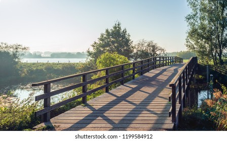 Simple wooden bridge with planks and a railing over the narrow Dutch river Donge in the early morning sunlight. It is autumn now and the colors are already changing.