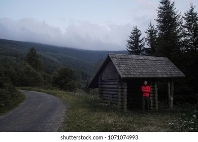 simple wooden cabin used as a hiking shelter with hiker standing inside, czech republic