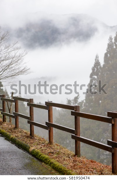 A simple wooden fence borders the cliffside, with trees and mountain partially visible through heavy fog and clouds in the background. Miyazaki, Japan. Travel and nature concept.
