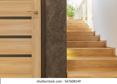 Simple wooden interior door and wooden staircase in wellness and spa center
