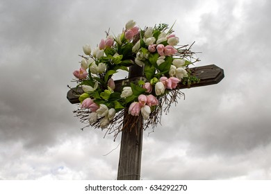 Simple Wooden Roadside Cross with a Wreath of White and Pink Silk Tulips
