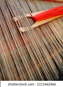 A simple wooden stick shuttle carries red yard through the warp of a traditional weaving loom.