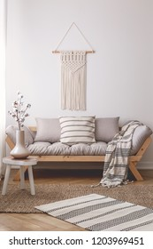 Simple, wooden stool on a wicker rug in a peaceful living room interior with a beautiful handmade decoration on a white wall