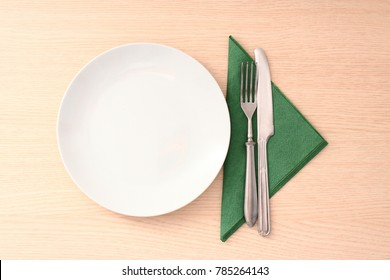 Simple wooden table with dish and cutlery.