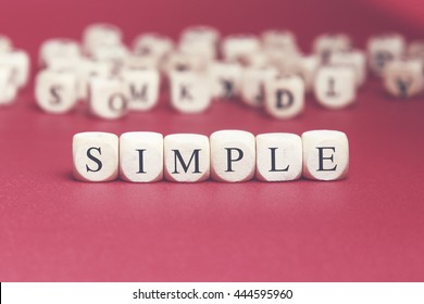 Simple word written on wood cube with red background