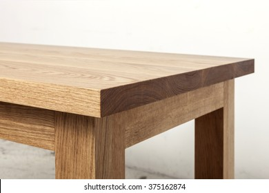 A simple(minimal) oak wood office desk(dining table) on the vintage white bottom, white wall.