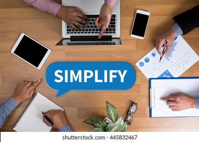 SIMPLIFY Business team hands at work with financial reports and a laptop, top view