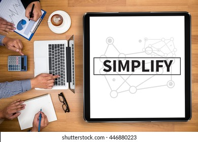 SIMPLIFY Business team hands at work with financial reports and a laptop