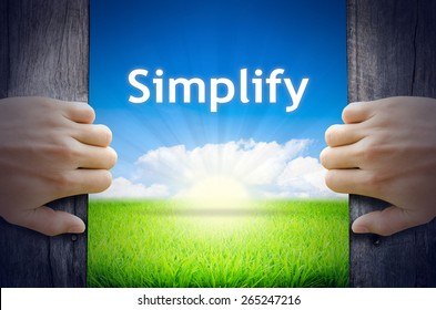 Simplify. Hands opening a wooden door then found a texts floating among new world as green grass field, Blue sky and the Sunrise.