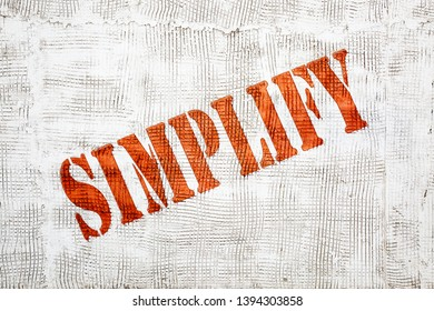 simplify - red graffiti style sign on a white stucco wall