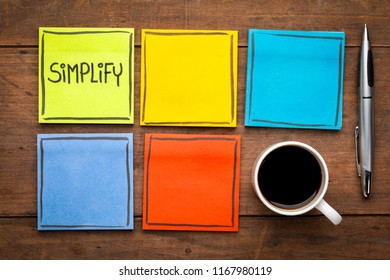 Simplify - task management concept. Handwriting on sticky notes against rustic wood board with a cup of coffee