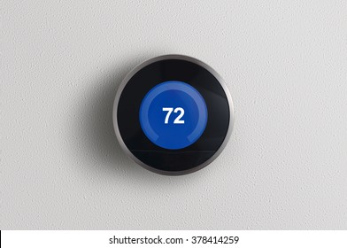 A simplistic photo of a round, modern, programmable digital thermostat, on a clean white wall in cooling mode.