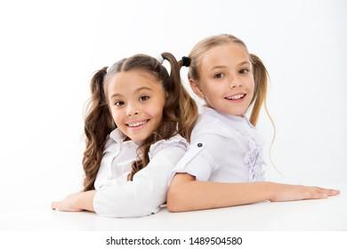 Simply beautiful. Cheerful smart schoolgirls. Happy schoolgirls isolated on white. Small schoolgirls smiling in school uniform. Cute schoolgirls with long ponytails and charming look.