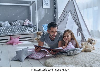 Simply being around. Father reading a book to his daughter while lying on the floor in bedroom