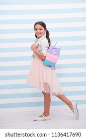 Simply cuteness. Child girl cute smiling face carry bag on shoulder. Kid long curly hair wear fashionable outfit. Girl with cute bag walks striped background. She likes try on fashionable outfits.