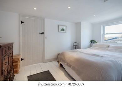 Simply decorated cottage bedroom in shades of white dominated by a double bed with quilt