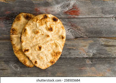 Simply delicious baked crusty whole grain naan flatbreads, a leavened bread cooked in a tandoor clay oven, served on authentic old wooden Picnic Table shot from above with copyspace on the right