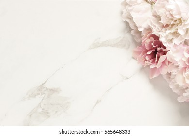 Simply elegant peony bouquet framing white marble background with room for copy.