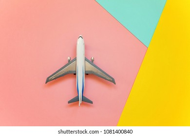Simply flat lay design with miniature toy model plane on blue, yellow and pink pastel colorful paper geometric background. Travel by plane vacation summer weekend sea adventure trip concept