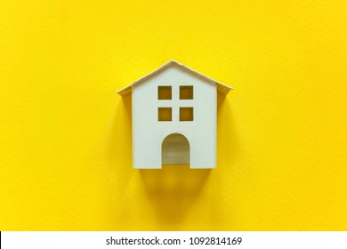 Simply flat lay design with miniature white toy house on yellow colorful paper trendy background. Mortgage property insurance dream home concept
