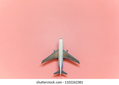 Simply flat lay design with miniature toy model plane pink pastel colorful trendy paper background. Travel by plane vacation summer weekend sea adventure trip concept