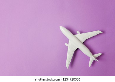 Simply flat lay design miniature toy model plane on violet purple pastel colorful paper trendy background. Travel by plane vacation summer weekend sea adventure trip journey ticket tour concept