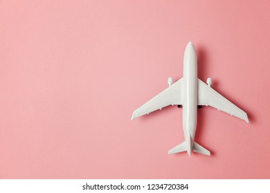 Simply flat lay design miniature toy model plane on pink pastel colorful paper trendy background. Travel by plane vacation summer weekend sea adventure trip journey ticket tour concept