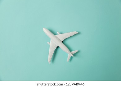 Simply flat lay design miniature toy model plane on blue pastel colorful paper trendy background. Travel by plane vacation summer weekend sea adventure trip journey ticket tour concept