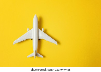 Simply flat lay design miniature toy model plane on yellow colorful paper trendy background. Travel by plane vacation summer weekend sea adventure trip journey ticket tour concept